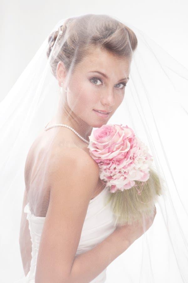 面纱的美丽的微笑的新娘与花束 免版税库存照片
