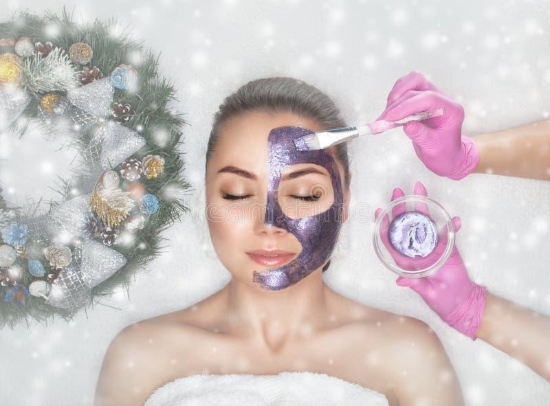 面罩美女的皮肤 她旁边是圣诞装饰 新年美容观 免版税库存图片
