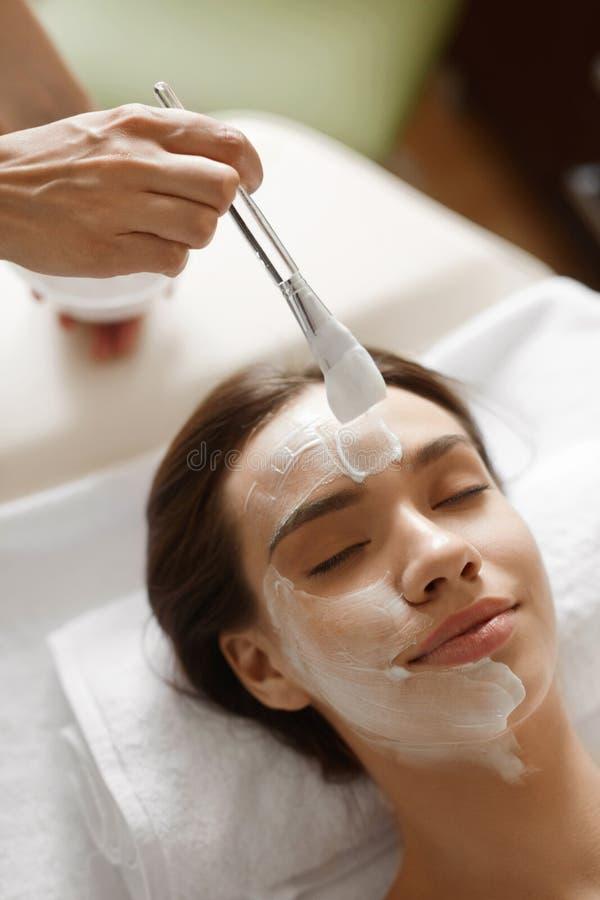面部秀丽治疗 得到化妆面具的美丽的妇女 免版税库存照片