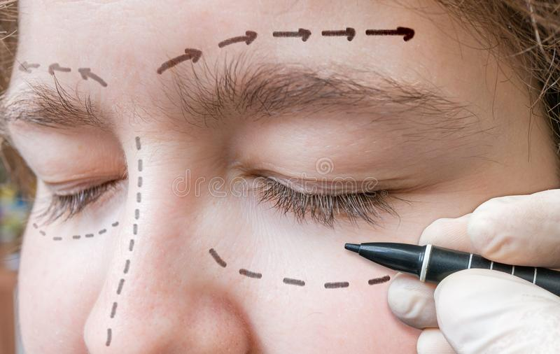 面部整容手术 手在眼睛附近画与标志的线 免版税图库摄影