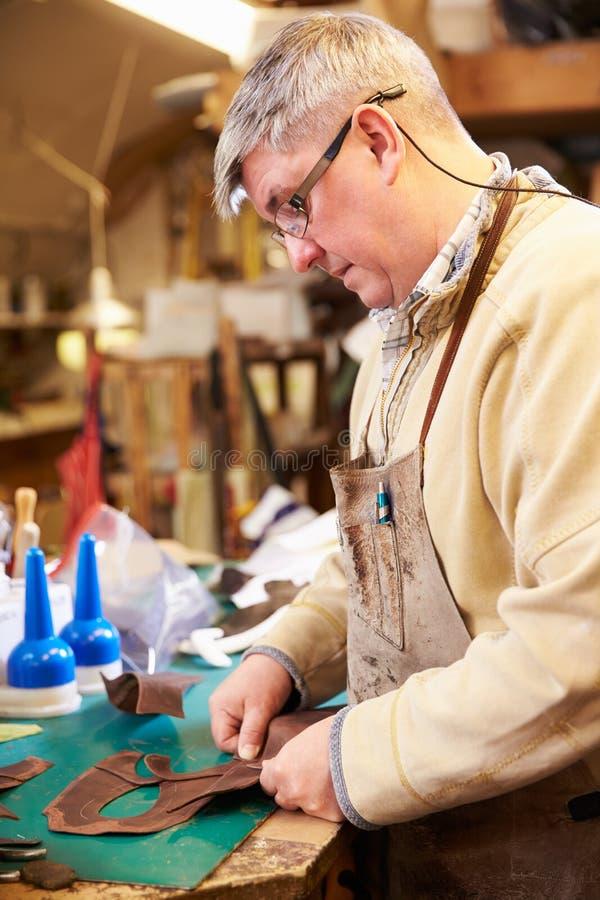 鞋匠切口和胶合皮革在车间 库存照片