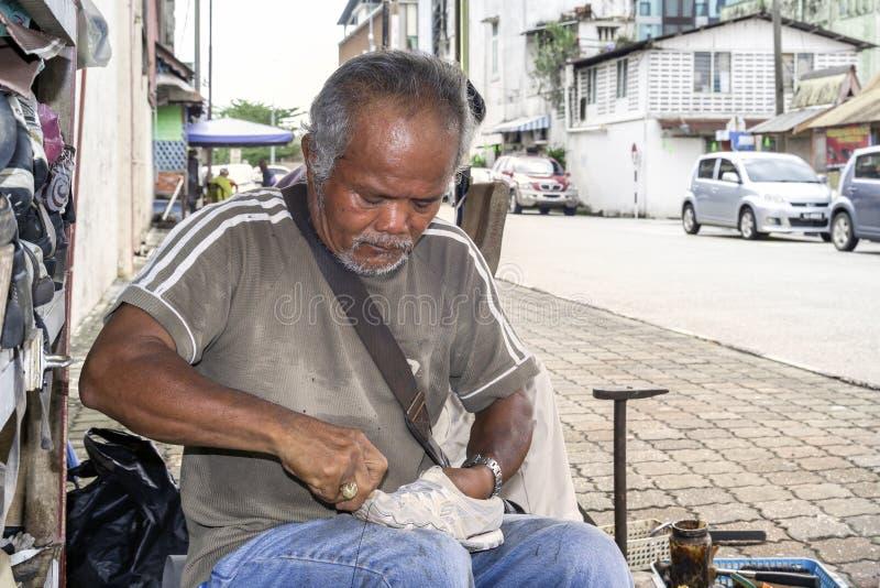 鞋匠在街道车间修理鞋子 免版税库存照片