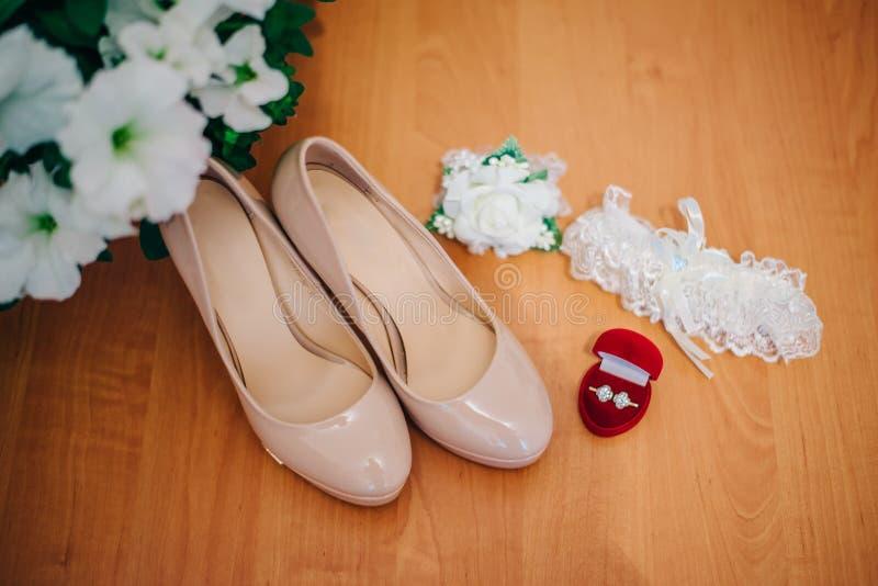 鞋子、新娘的婚戒和袜带 免版税库存照片