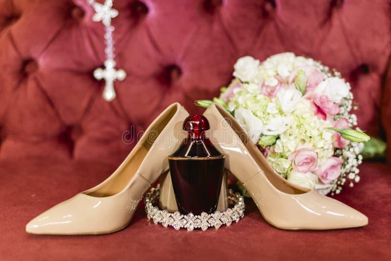 鞋子、新娘的香水和花束细节  库存照片