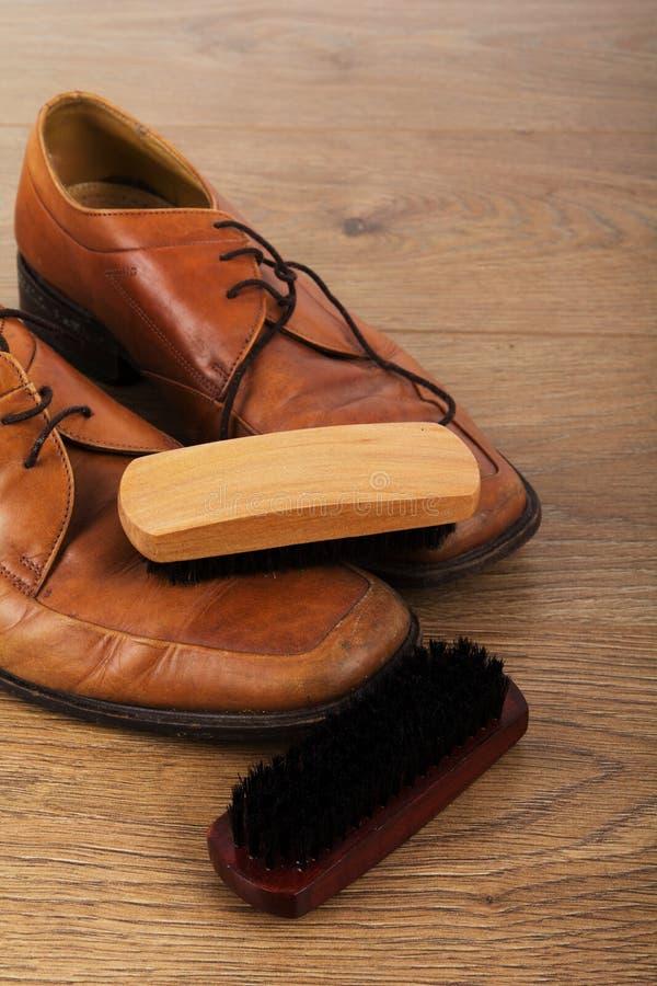 鞋子和清洁设备在一个木地板上 库存图片