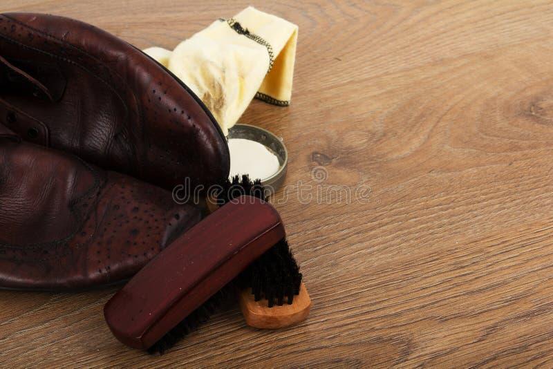 鞋子和清洁设备在一个木地板上 图库摄影