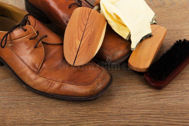 鞋子和清洁设备在一个木地板上 免版税库存照片