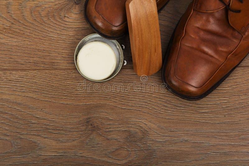 鞋子和清洁设备在一个木地板上 免版税库存图片
