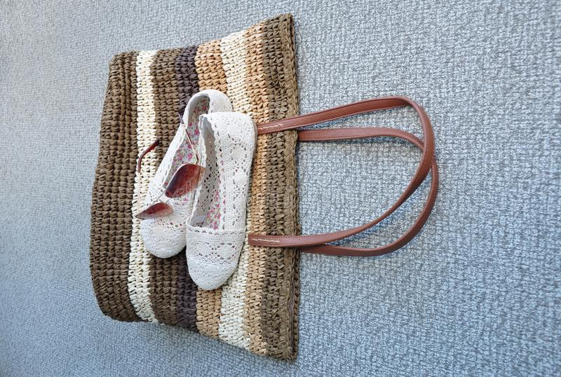 鞋子和sunglass在秸杆袋子 库存照片