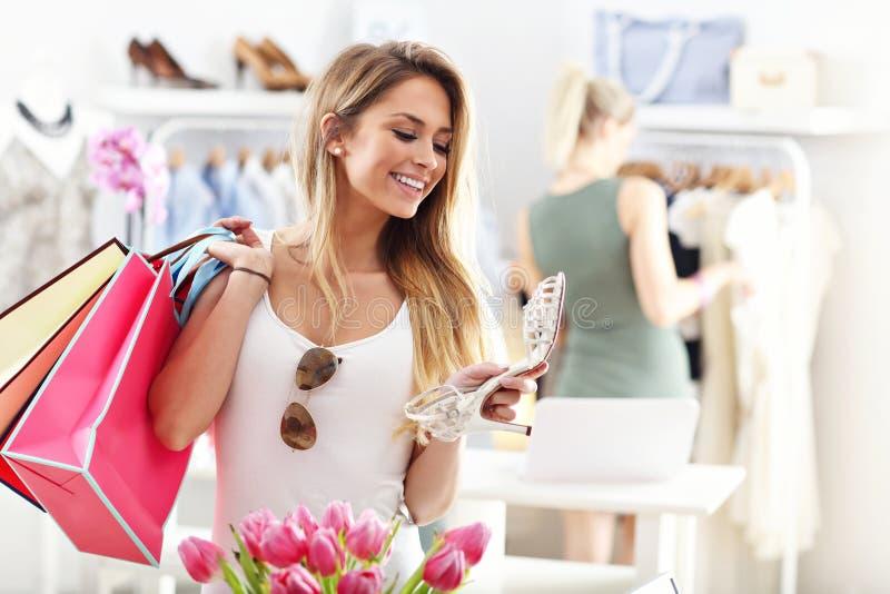 鞋子的愉快的妇女购物 免版税库存照片