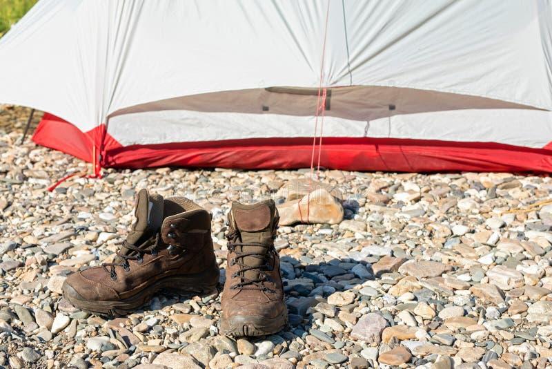鞋子选择旅游业和迁徙的 布朗起动在小卵石站立在帐篷附近 库存图片