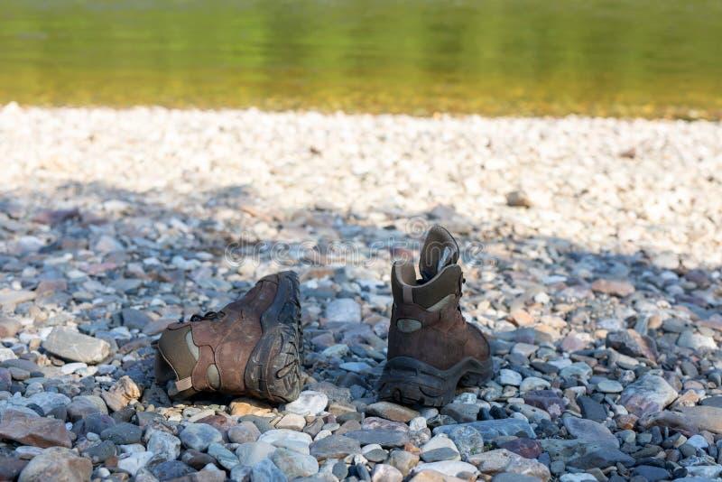 鞋子选择迁徙和旅游业的 布朗起动在石银行站立 库存照片