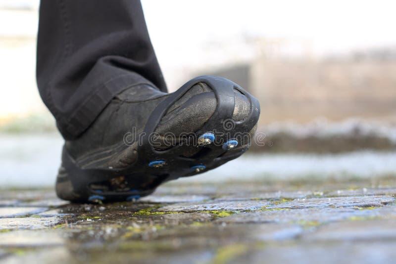 鞋子雪钉牢在道路的链子 库存图片