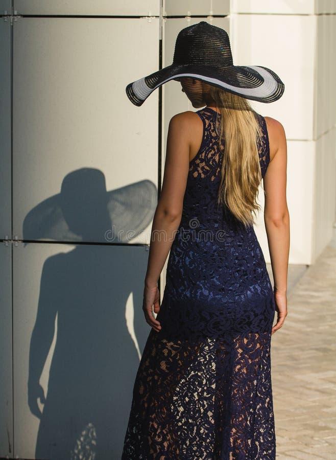 黑鞋带礼服和帽子的少妇有一个宽边缘的 免版税库存照片