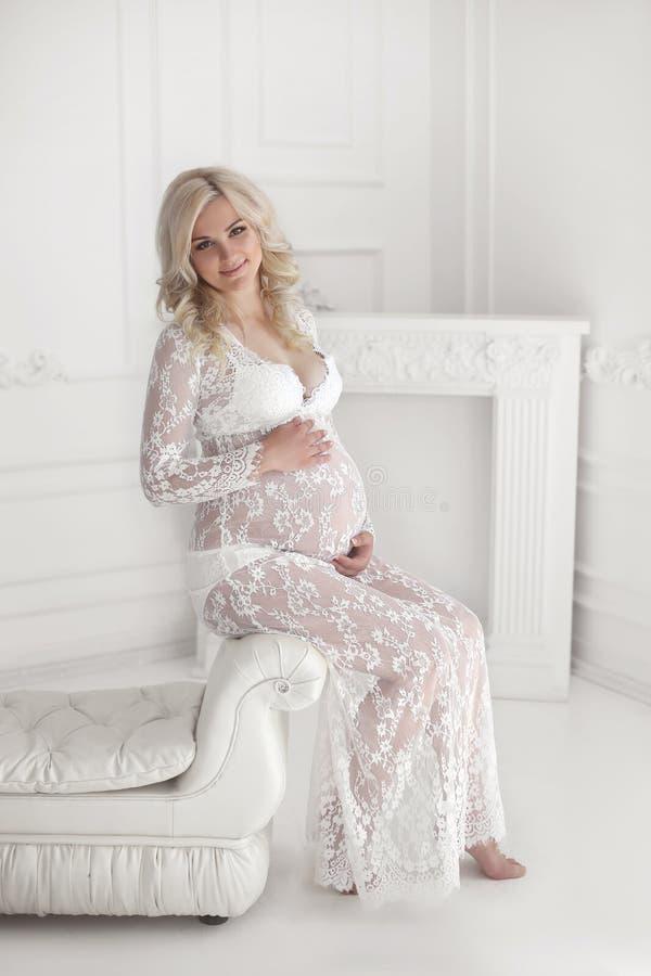 鞋带礼服的美丽的微笑的孕妇坐沙发, 免版税图库摄影