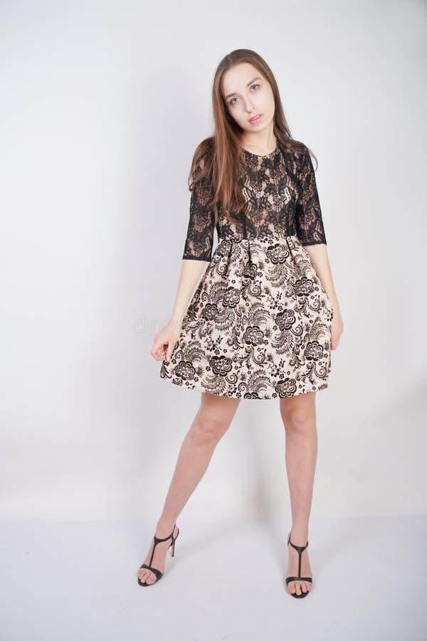 鞋带礼服的逗人喜爱的女孩在白色背景站立在演播室 免版税库存图片
