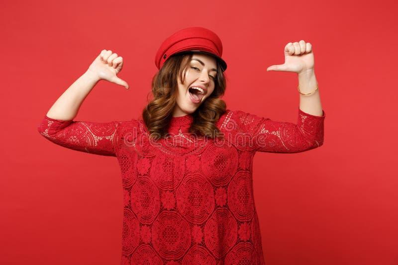 鞋带礼服盖帽的指向在她自己的快乐的确信的年轻女人画象拇指在明亮的红色墙壁上隔绝了 免版税图库摄影