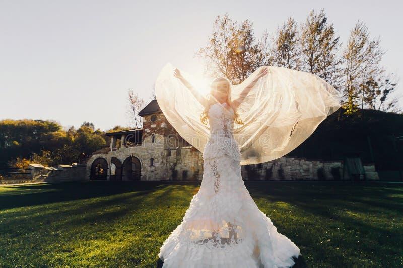 鞋带礼服backgroung墙壁的白肤金发的新娘在庭院里 免版税库存照片