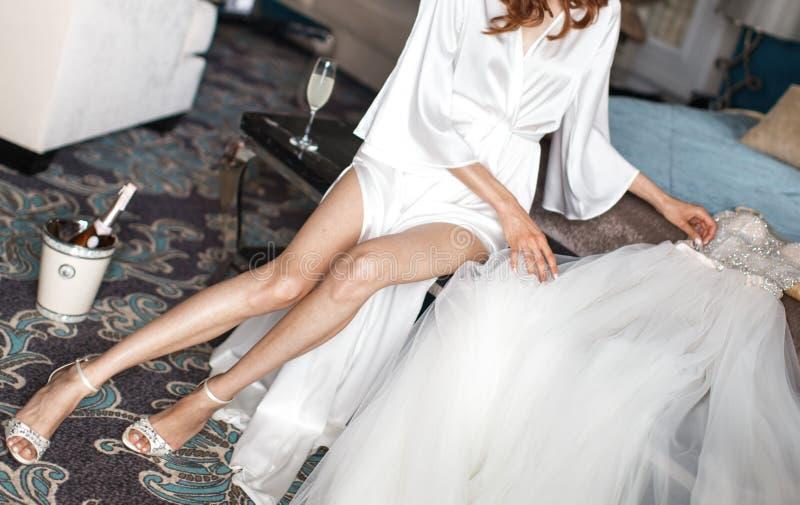 鞋带长袍和weding的礼服的新娘在床上 库存图片