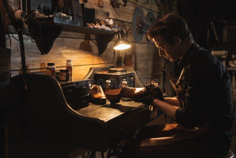 鞋类车间的被集中的人鞋匠 免版税库存图片
