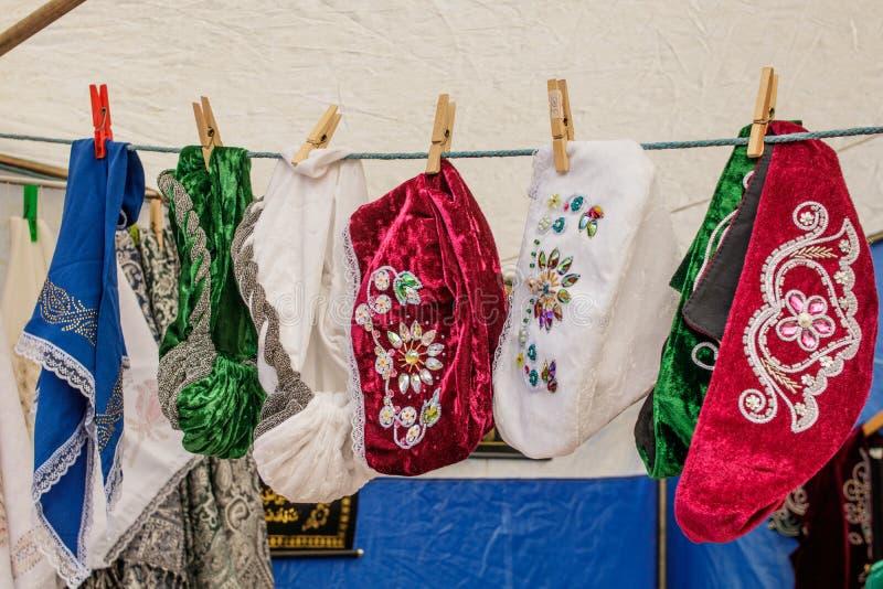 鞑靼人和巴什基尔人女性传统葡萄酒帽子垂悬在晒衣夹的待售在绳索 免版税图库摄影