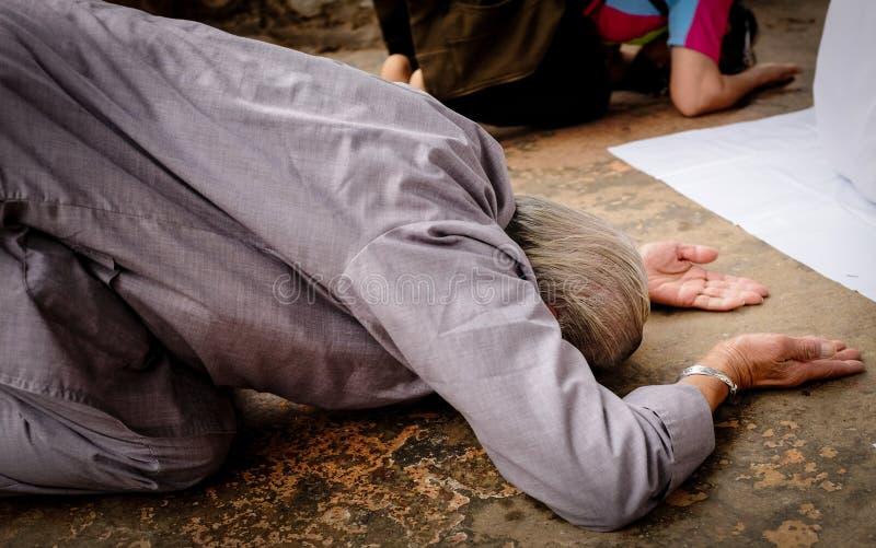 鞠躬佛教的崇拜者祈祷,下跪和致以尊敬 库存图片