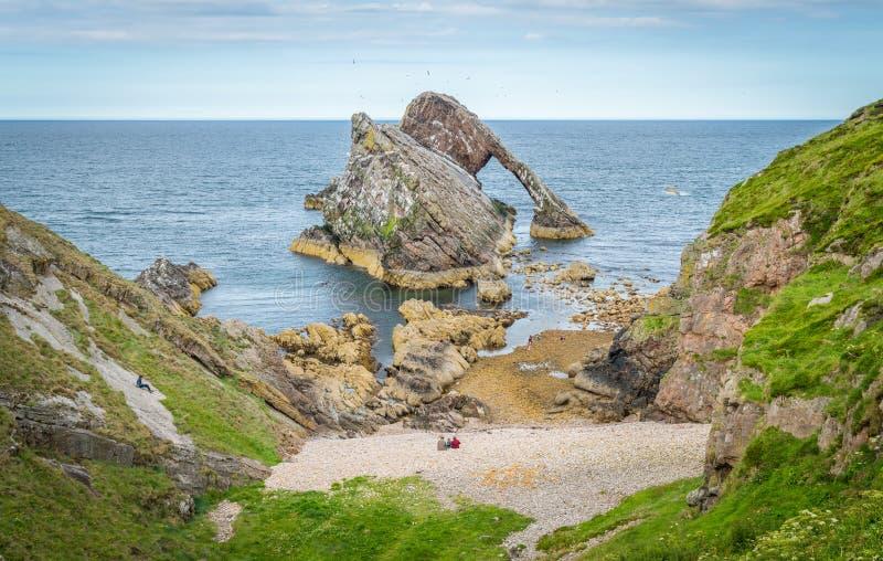 鞠躬无意识而不停地拨弄岩石,在Portknockie附近的自然海曲拱在苏格兰的东北海岸 免版税图库摄影