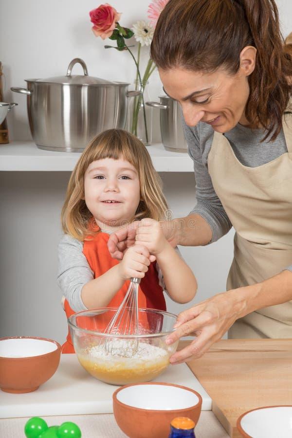 鞭打的孩子看和做与母亲的一个蛋糕 免版税图库摄影