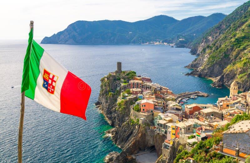 韦尔纳扎村庄五颜六色的房子、帝堡城多利亚城堡在岩石峭壁和意大利旗子前景,热那亚海湾,利古里亚海,Natio 库存图片