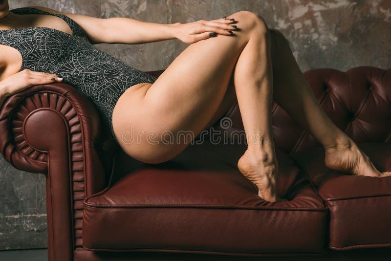 韧性适合腿臀部和屁股 摆在反对沙发的豪华泳装身体的美丽的运动的女孩 垂直 库存照片