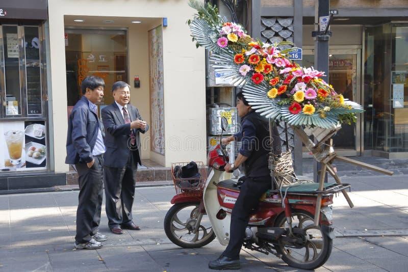 韩国人与交付花,汉城韩国2013年11月的摩托车的人谈话 免版税库存图片