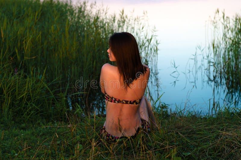 韩国女孩坐池塘在晚上 库存照片