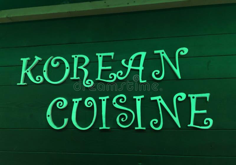 韩国烹调氖唱歌在木墙壁上 库存图片