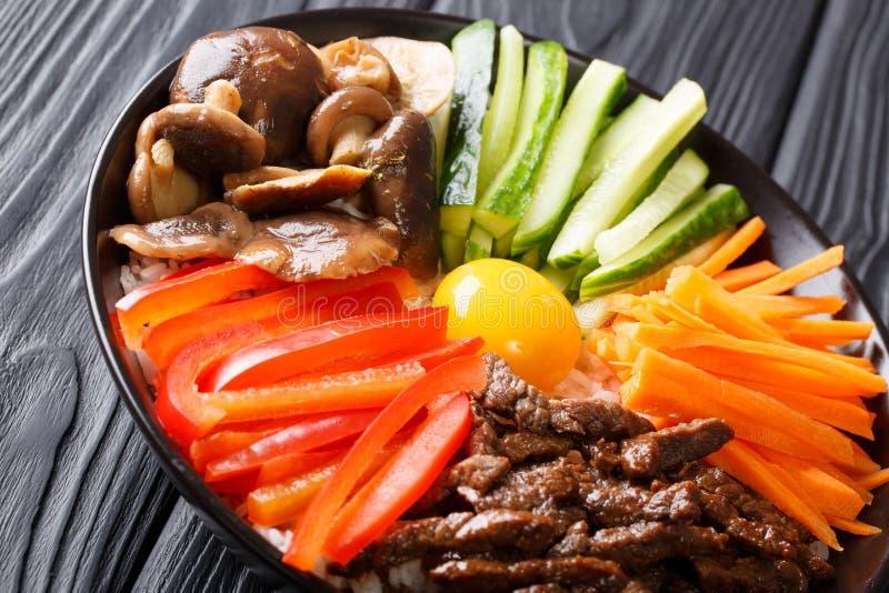 韩国食物朝鲜拌饭用油煎的牛肉,未加工的鸡蛋,菜, shiit 库存图片