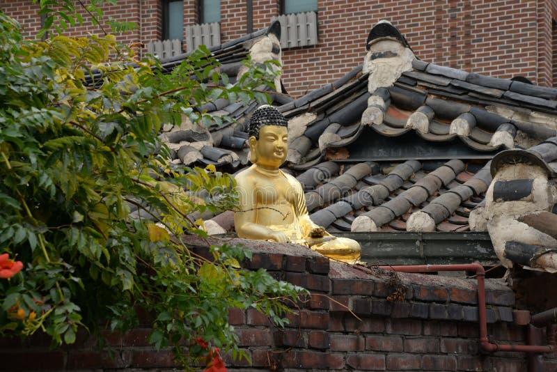 韩文传统结构 在屋顶的金黄菩萨雕象 免版税库存图片