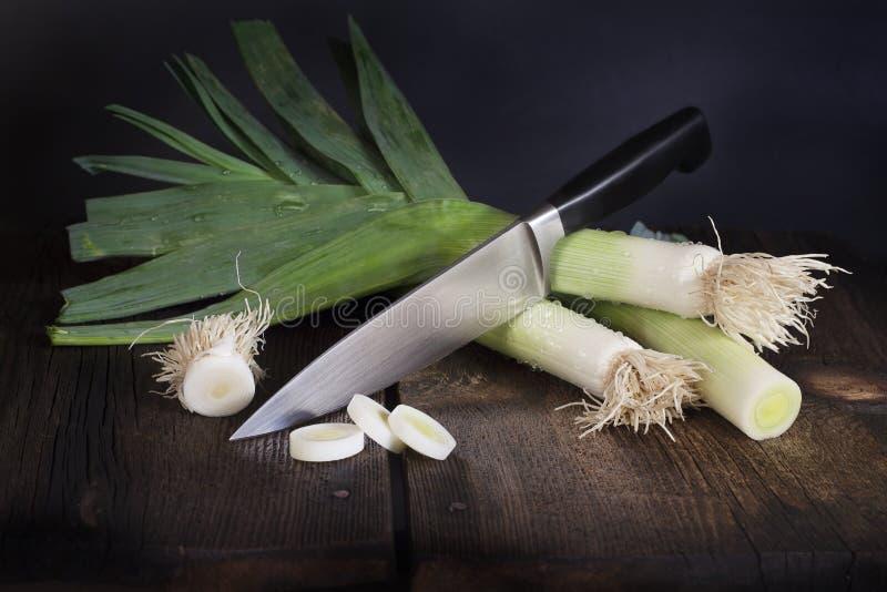 韭葱和厨师刀子 免版税图库摄影