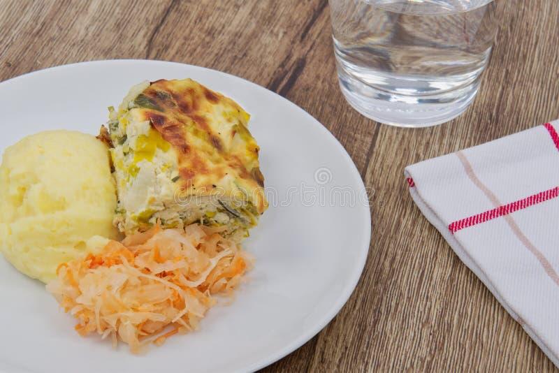 韭葱烤宽面条和土豆饲料在桌上 库存图片