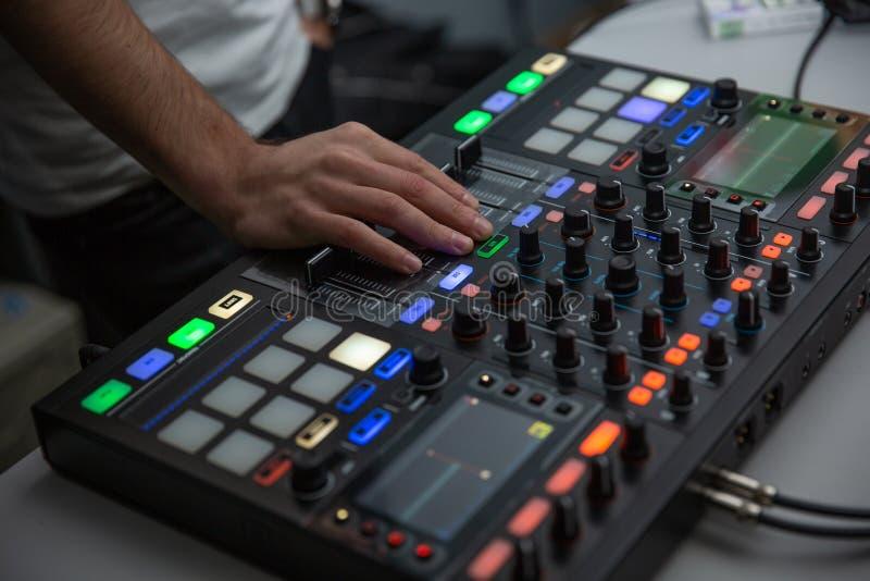 音乐、技术、人和设备概念-使用混合的控制台的人 图库摄影