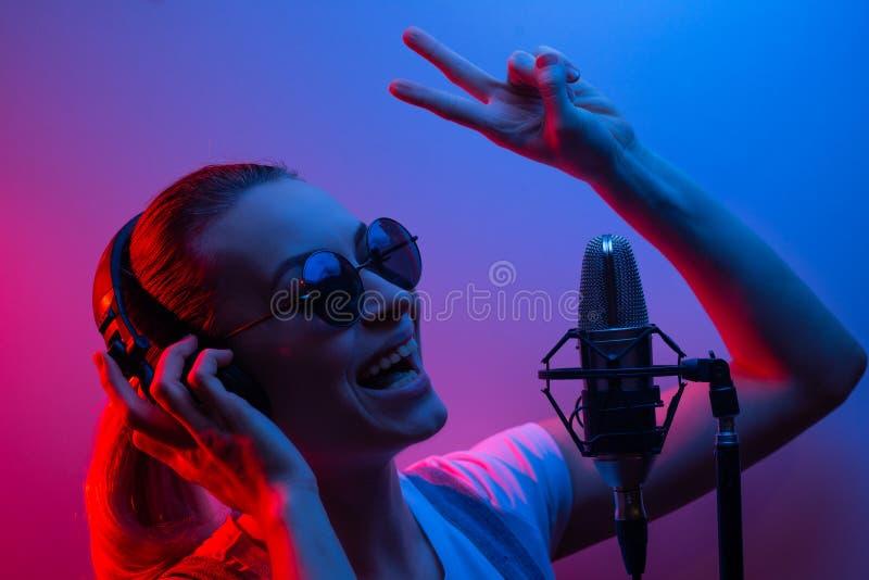 音乐、演艺界、人们和有耳机有玻璃的和话筒的唱一首歌曲在的歌手或DJ的声音 图库摄影