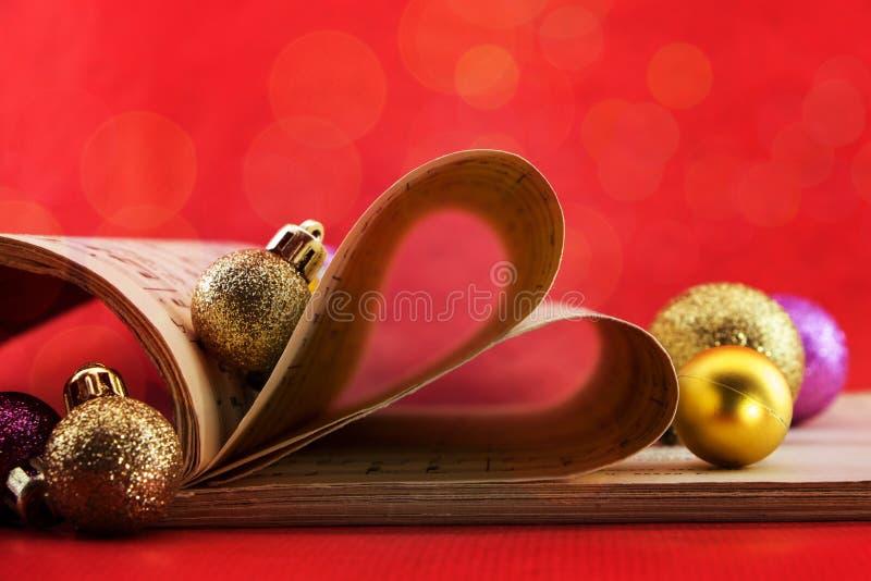 音乐与塑造心脏和圣诞节装饰品的页的记法书 库存图片