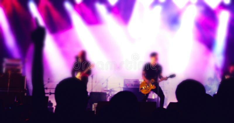 音乐会人群剪影在举他们的在明亮的阶段光的节日人群背面图的手 图库摄影