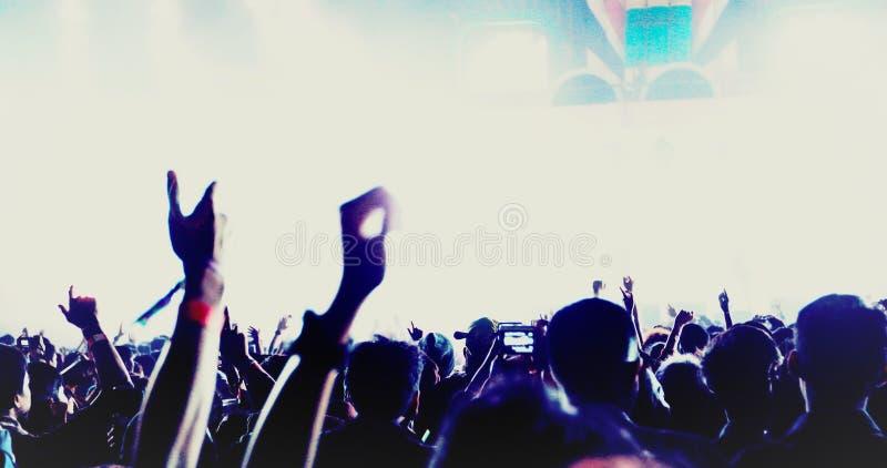 音乐会人群剪影在举他们的在明亮的阶段光的节日人群背面图的手 免版税库存照片