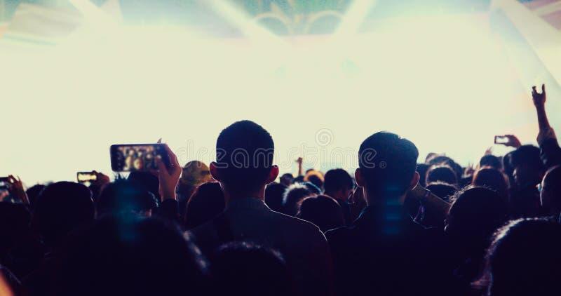音乐会人群剪影在举他们的在明亮的阶段光的节日人群背面图的手 免版税库存图片