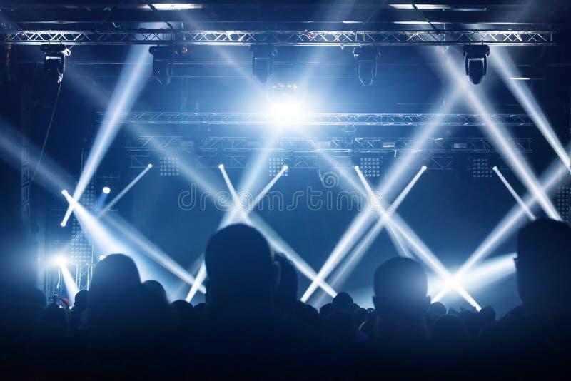音乐会人群 在明亮的阶段光前面的人剪影 摇滚明星带  库存图片