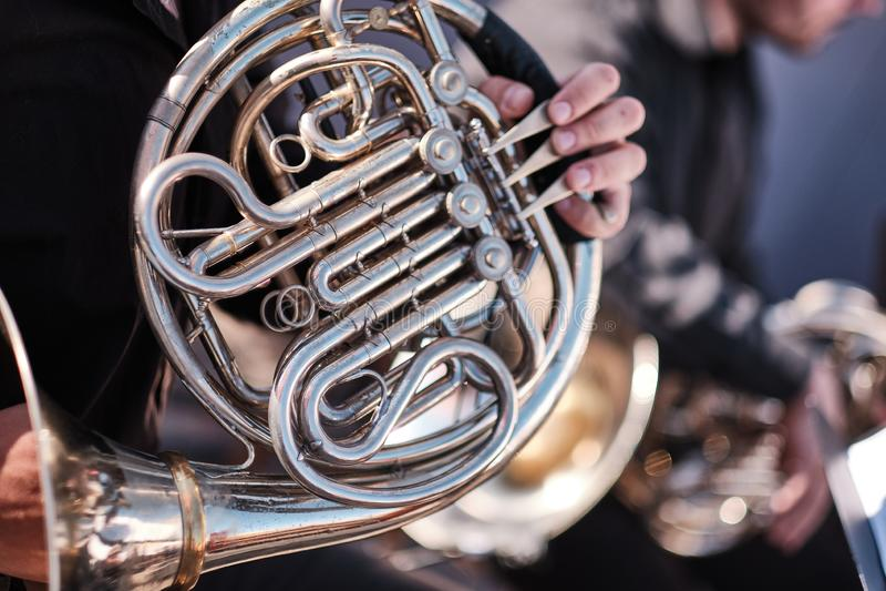 音乐家喇叭演奏员在交响乐团执行他的音乐部分 无法认出,特写镜头、一部分的身体和手 黄铜 库存图片