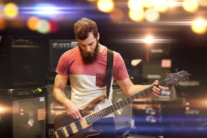 音乐家或顾客有吉他的在音乐商店 免版税库存照片