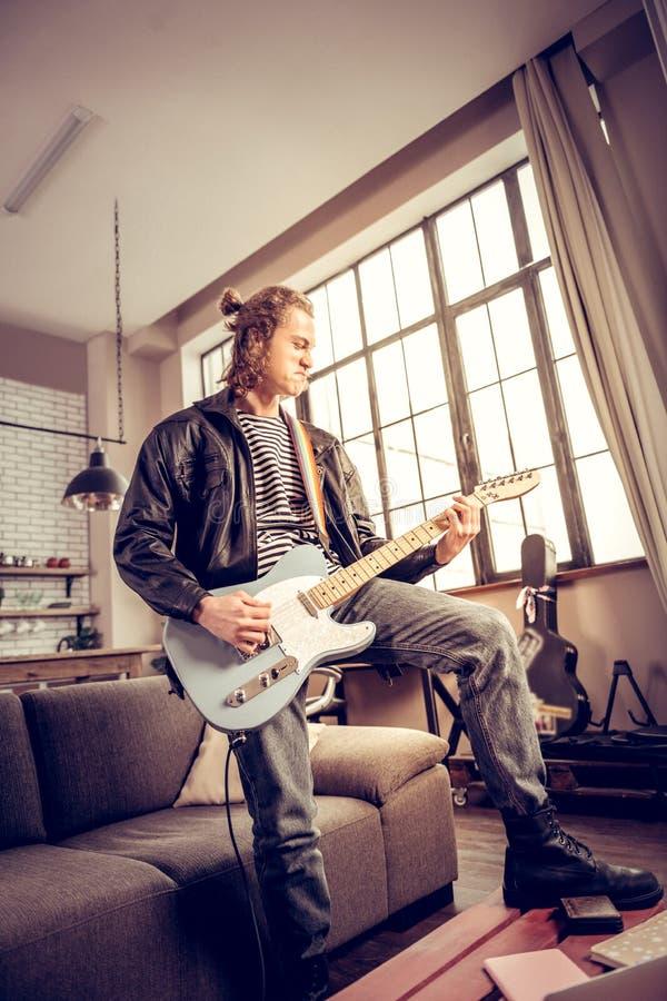 音乐家用得到满意的头发小圆面包演奏摇滚音乐 免版税库存图片