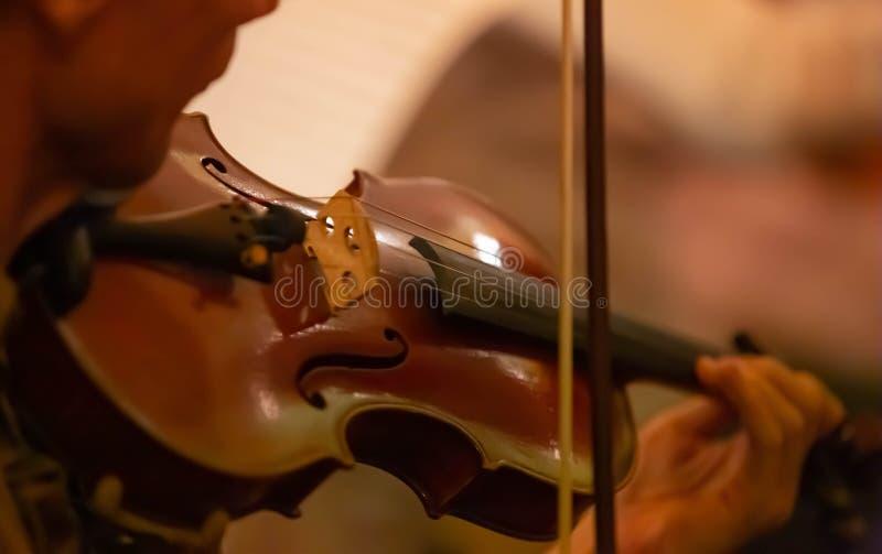 音乐家的手的特写镜头弹在乐队的一把小提琴 库存照片