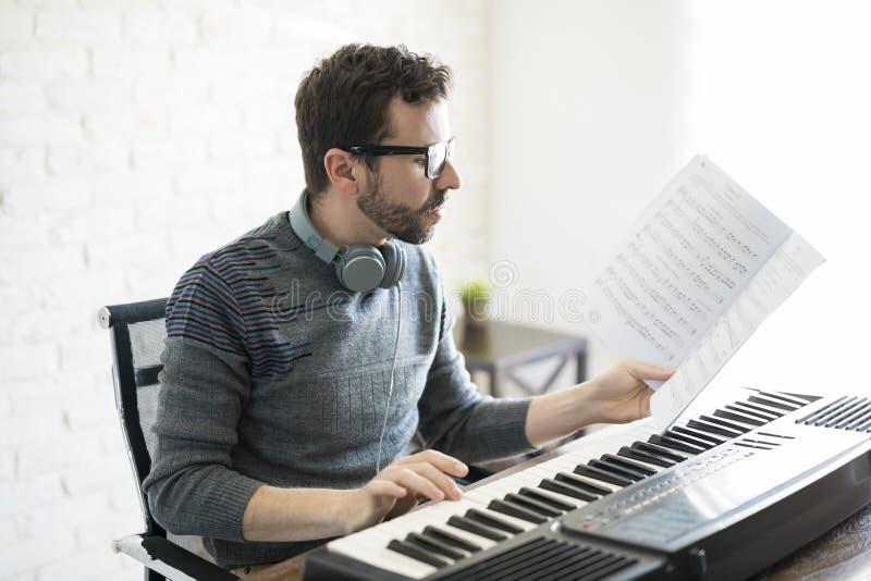 音乐家读书音乐纸张和使用钢琴 图库摄影