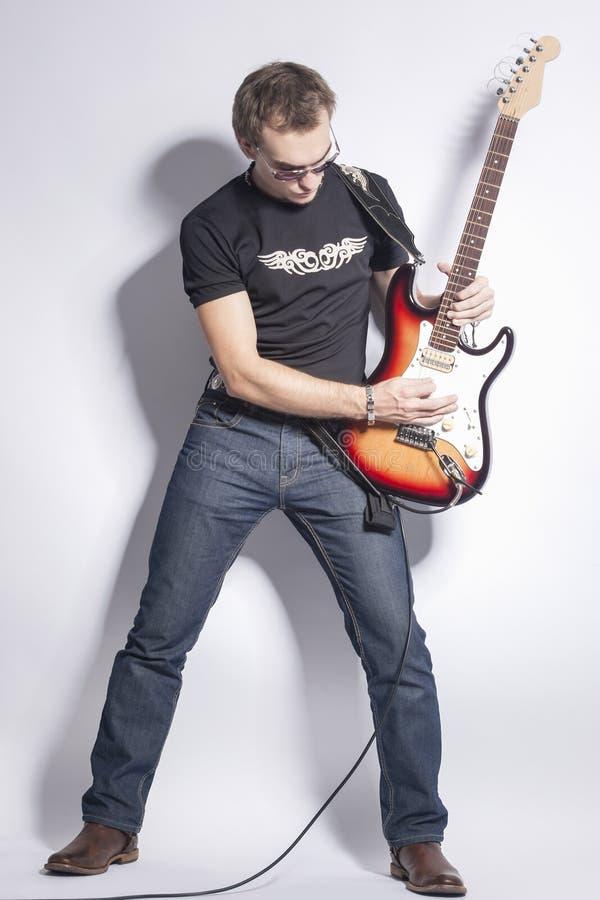 音乐想法和概念 传神摆在与吉他的男性吉他演奏员反对白色 免版税图库摄影